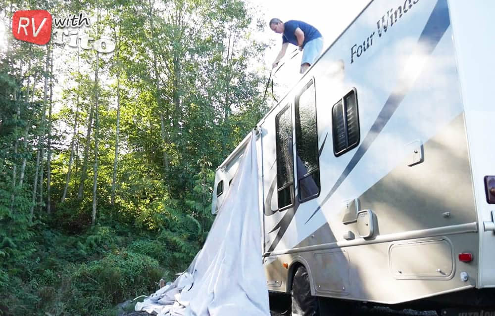 You can use a strap to pull your RV cover up onto the roof | Photo by RVWithTito.com